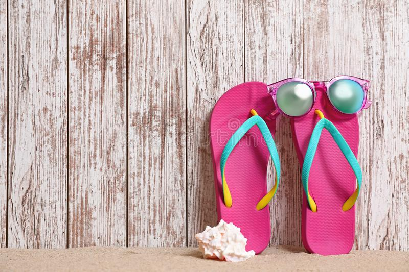 Bright flip flops and sunglasses on sand near  wall, space for text. Summer beach accessories stock image
