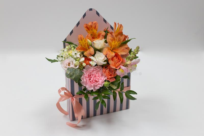 Bright floral arrangement of fresh flowers in a box in the form of an envelope on a light background. Flowers: carnation, rose, alstroemeria, leaves. Colors royalty free stock image