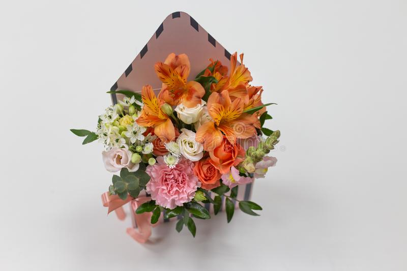 Bright floral arrangement of fresh flowers in a box in the form of an envelope on a light background. Flowers: carnation, rose, alstroemeria, leaves. Colors stock photo