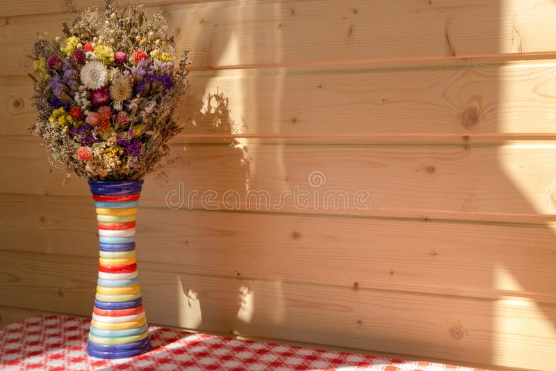 Bright flowers in colorful vase against wooden panel wall on red and white checked tablecloth. stock photo