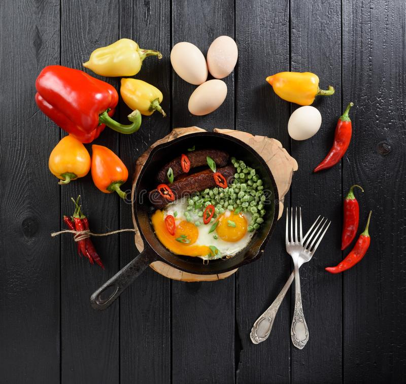 Bright food flatlay. Organic eggs, sausages and peas fried in ca. St iron pan served with chili and bell peppers on black wooden background overhead view royalty free stock images