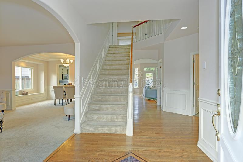 Bright foyer with white walls and staircase. Lined with a board and batten trim stock photography