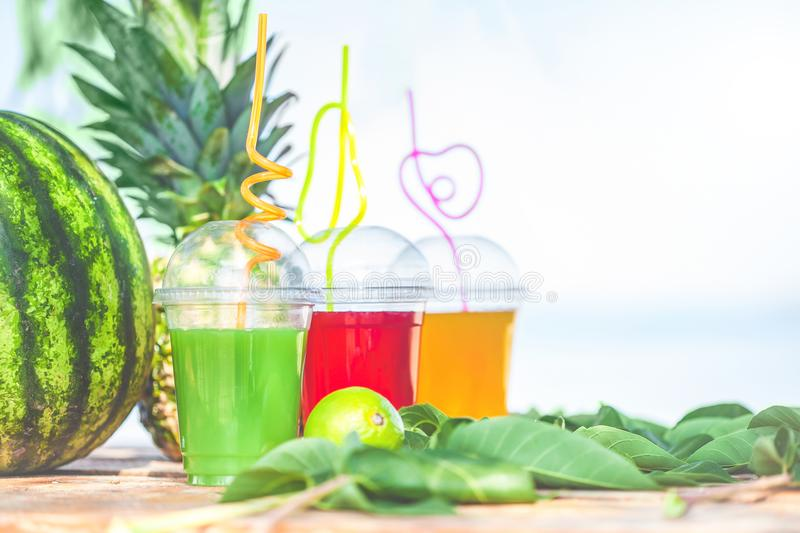 Bright Fresh healthy juices, fruit, pineapple, watermelon on the background of the sea. Summer, rest, healthy lifestyle royalty free stock images