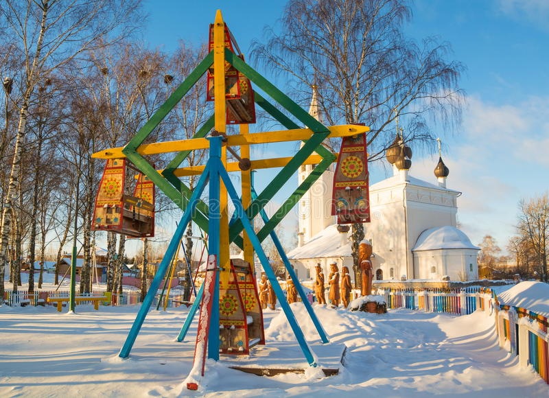 Bright frosty day. Russian winter landscape with wooden carousels and with church royalty free stock images