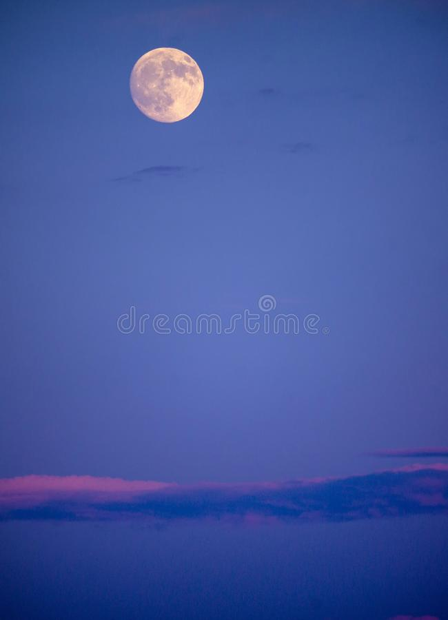 Bright full moon in early evening sky with long, pink-tinged cloud bank below royalty free stock photography