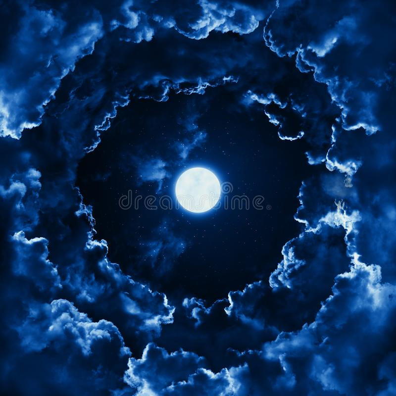 Bright full moon in the mystical midnight sky with stars surrounded by dramatic clouds. Dark natural background with night sky royalty free stock photography