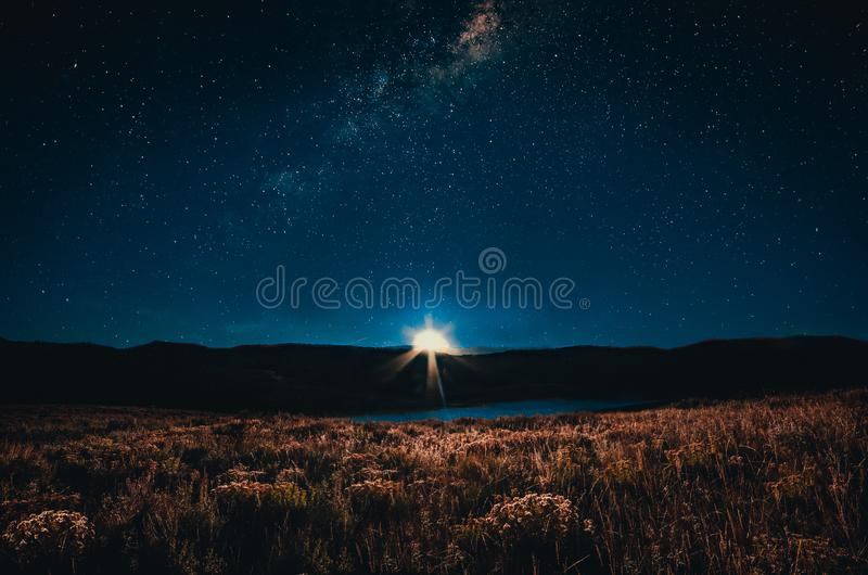 Bright full moon rising over the mountains and milky way stock image