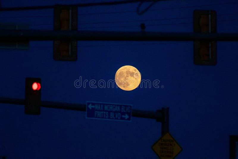 Full moon rising in between street lights royalty free stock photos