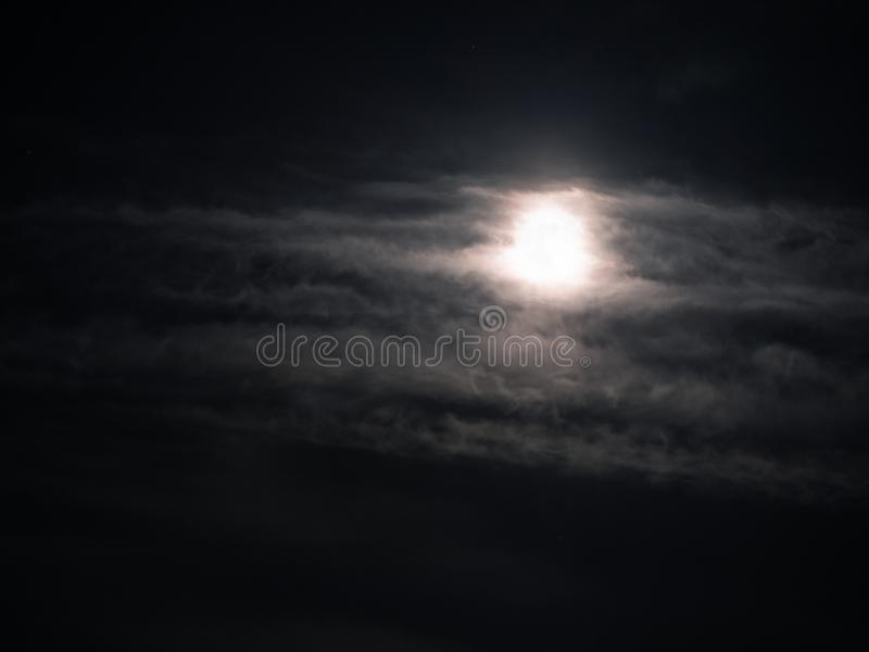 Cloudy night sky with a full moon shining bright stock image