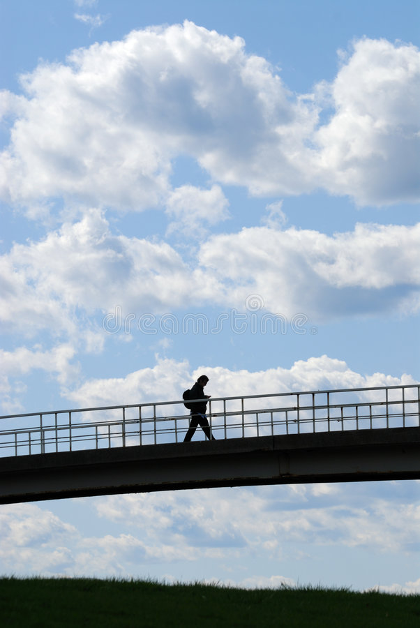 Bright Future. College student crossing bridge against bright blue sky royalty free stock image