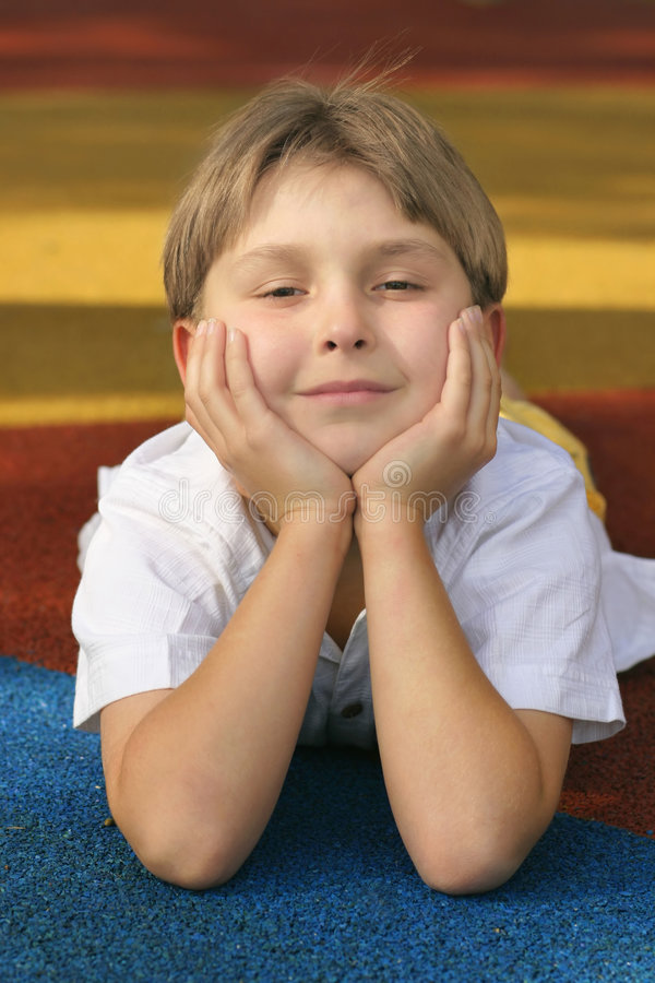 Bright future. A boy on colourful playground matting with a happy disposition/outlook stock photo