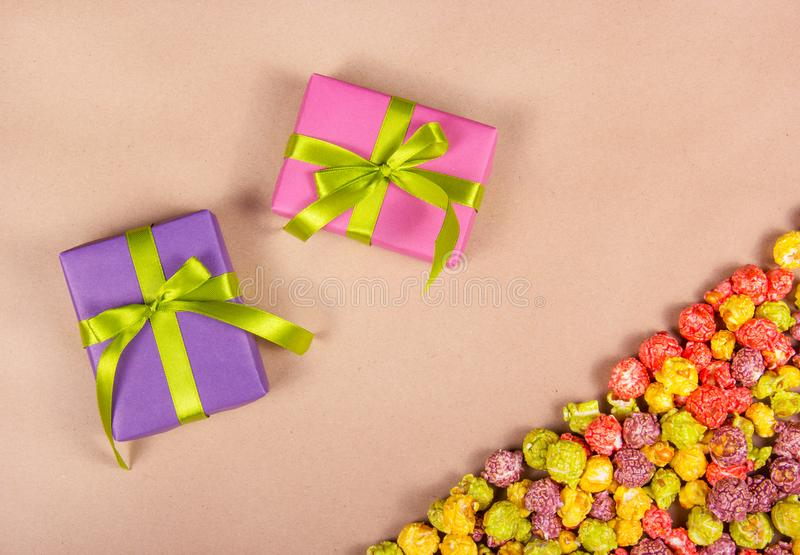 Bright gift boxes and colorful caramel popcorn on a paper background. Celebratory concept. royalty free stock photo