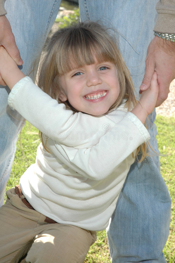 A Bright Girls smile. A beautiful little blond girl with blue eyes smiles and laughs as she crosses her arms in dads hands royalty free stock photography