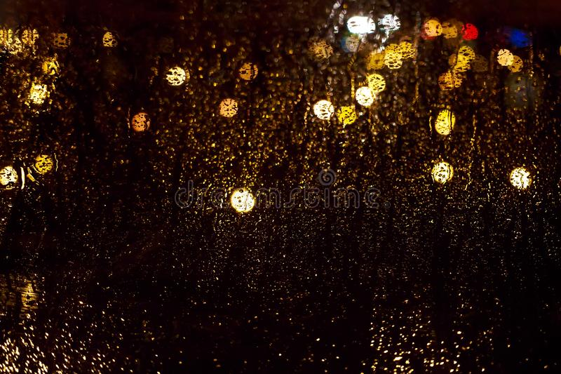 Bright glowing bokeh on wet glass against background of the nigh stock photo