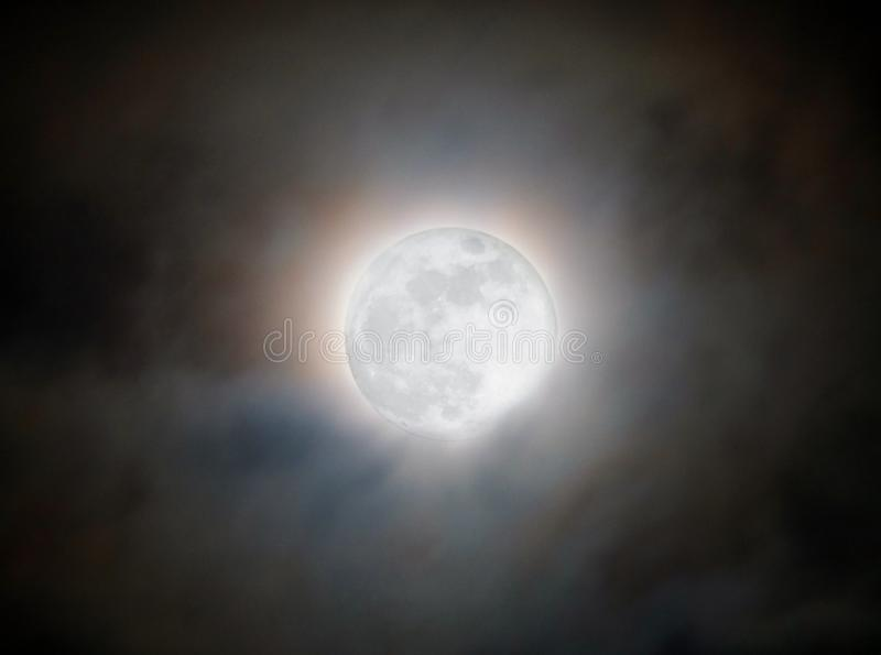 Bright glowing moon though clouds on the night of the super blue moon january 31 2018 stock image