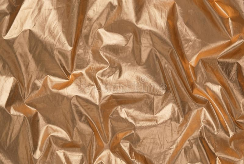 Bright gold textile, trendy holographic golden foil background royalty free stock photo