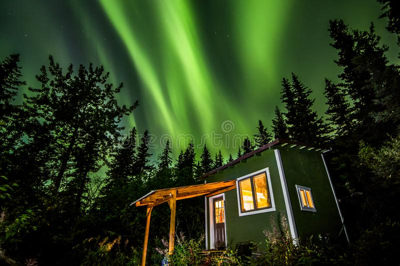 Bright green Aurora Borealis over small green and white tiny house in Alaska royalty free stock images
