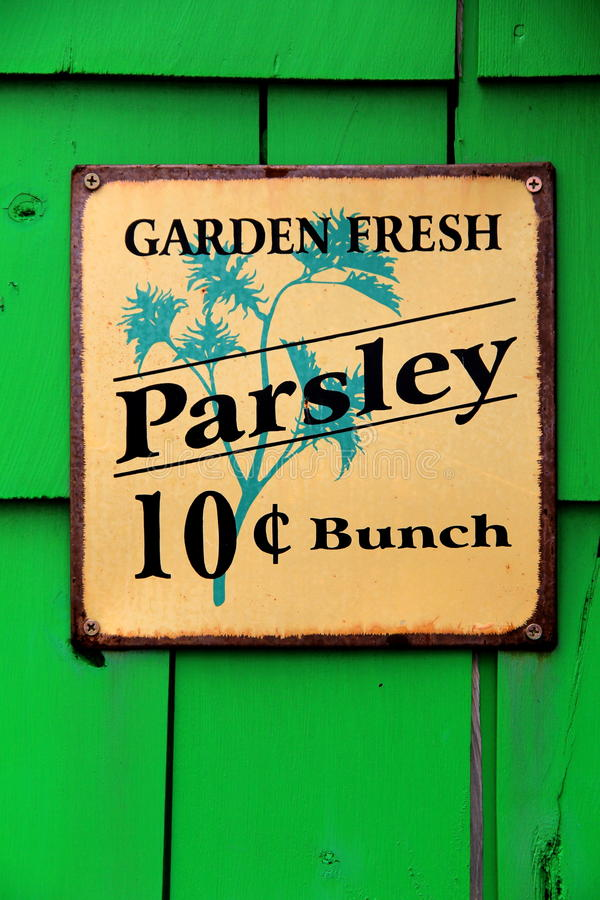 Bright green background with colorful metal sign selling Parsley. Bright green shingle background with colorful metal sign attached, advertising the sale of stock photography