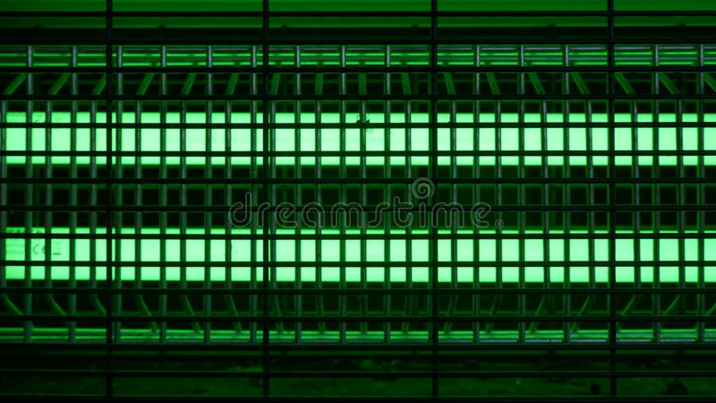Bright green glowing UV lamp. Electric insect trap royalty free stock photos