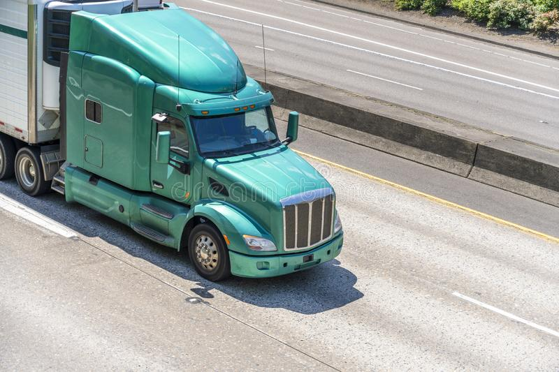 Bright green powerful big rig semi truck transporting cargo in refrigerated semi trailer driving on highway. Bright green powerful professional American bonnet stock image