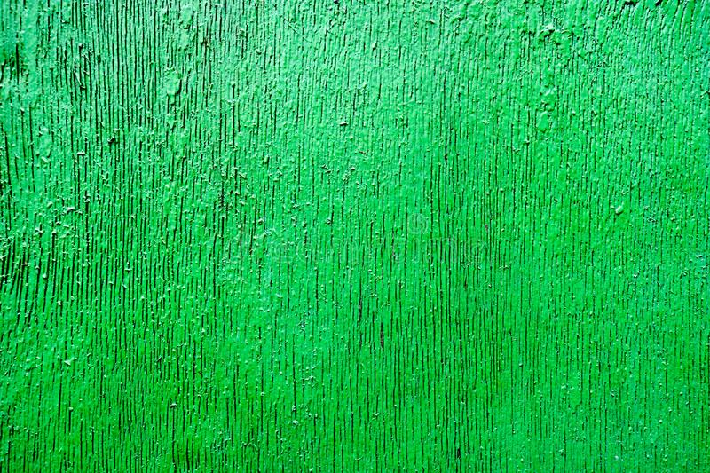 Bright green saturated relief texture beautifully painted with wood paint with vertical stripes, cracks, beautiful pattern royalty free stock photos