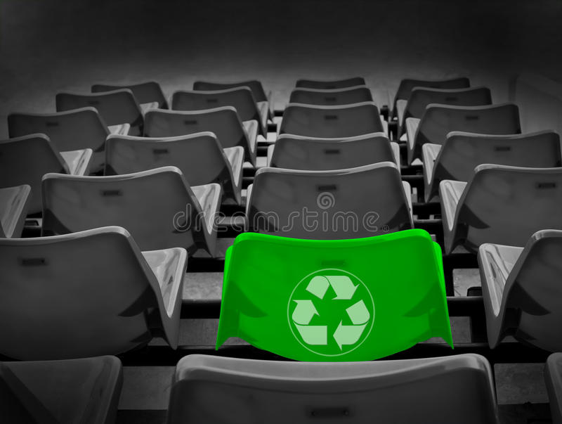 Bright green seat and recycle sign. Bright green seat in football stadium and recycle sign for green world concept royalty free stock photo