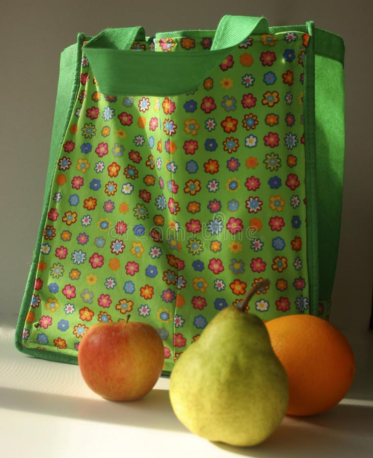 Bright green shopping bag with multicoloured funky floral pattern on the front and fruit in the foreground. Image of a bright green shopping bag with royalty free stock photo
