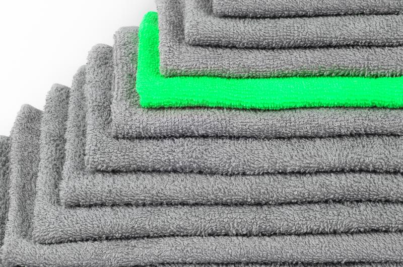 Bright green terry towel in stack of other gray ones. colour contrast. Bright green terry towel in a stack of other gray ones. white background. color conceptual stock images