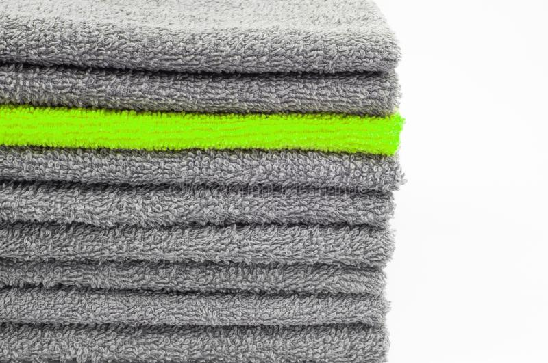 Bright green terry towel in stack of other gray ones. white background. color conceptual contrast. Bright green terry towel in a stack of other gray ones. white royalty free stock images