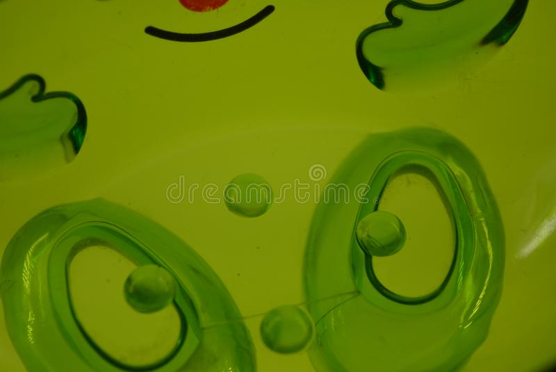 Bright green transparent plastic soap dish with a smile on a white background. royalty free stock photography