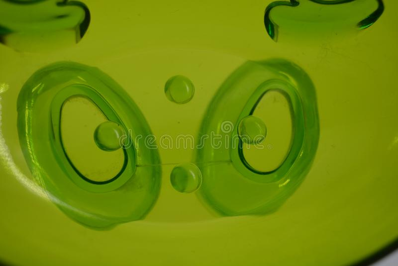Bright green transparent plastic soap dish with a smile on a white background. stock images