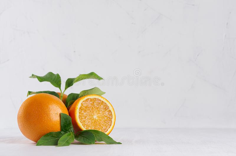 Bright group oranges with fresh green leaf and piece on soft light white modern interior. stock image