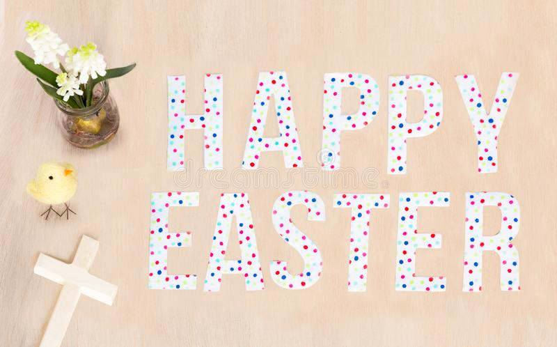 Bright Happy Easter text, chick, flowers, wood cross and background. Copy space. royalty free stock image