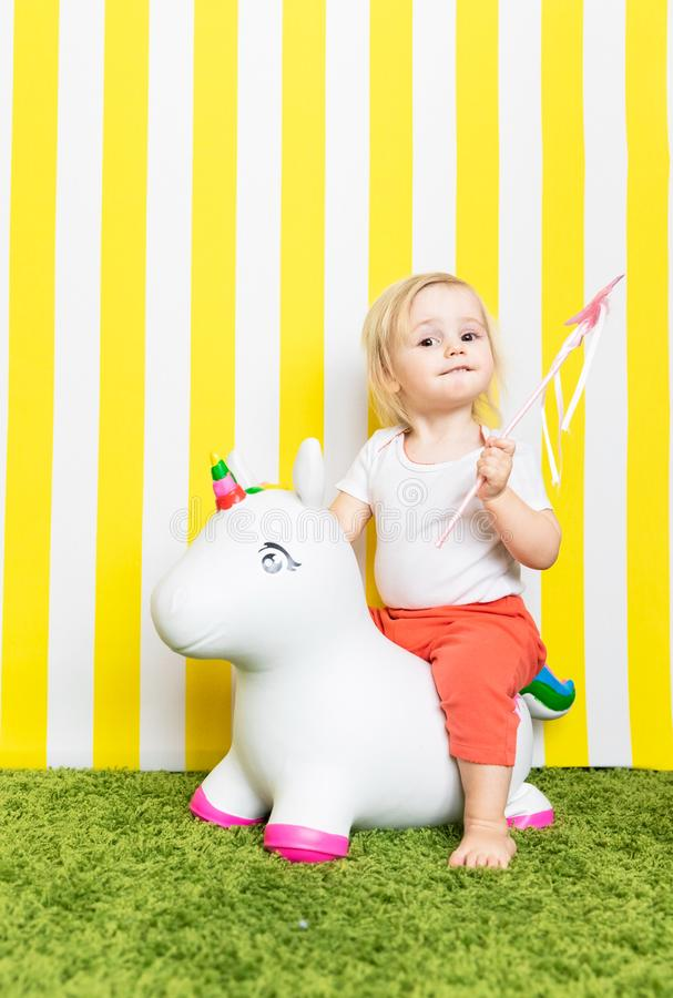 Bright Happy Little Girl on Toy Unicorn. Childhood. Background royalty free stock image