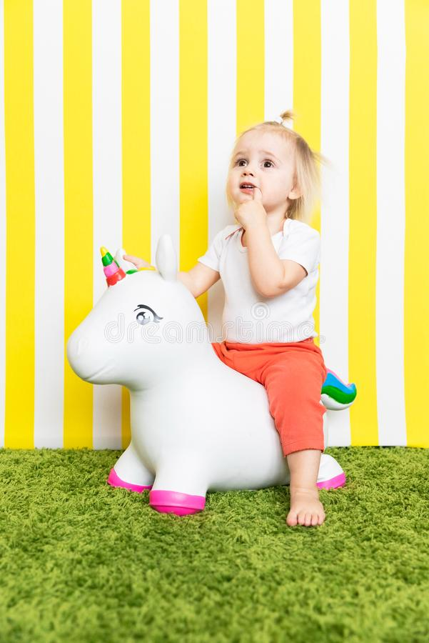 Bright Happy Little Girl on Toy Unicorn. Childhood. Background royalty free stock photography