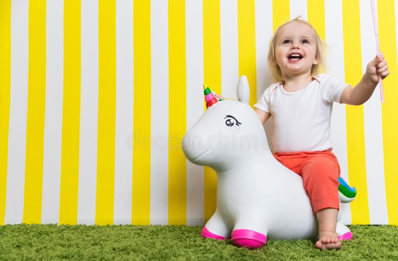 Bright Happy Little Girl on Toy Unicorn. Childhood. Background stock photos