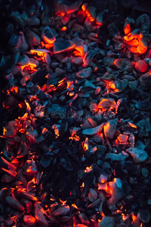 Bright hot coals and burning woods in bbq grill pit. Glowing and flaming charcoal, barbecue, red fire and ash. Weekend background. Bright hot coals and burning stock images