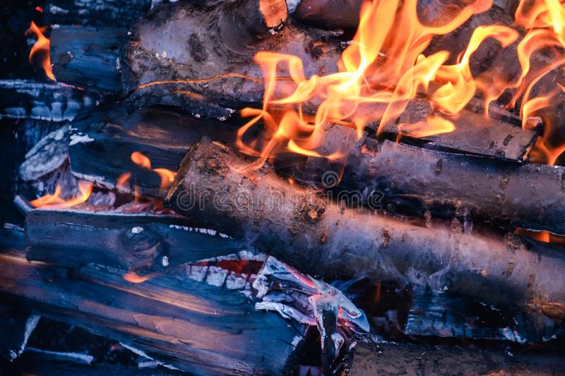 Bright hot coals and burning woods in bbq grill pit. Glowing and flaming charcoal, barbecue, red fire and ash. Weekend recreation background. Close-up, top stock images