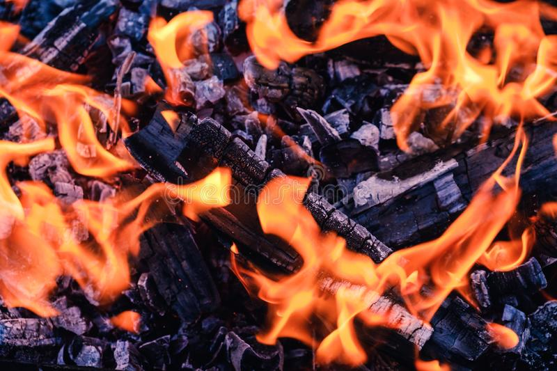 Bright hot coals and burning woods in bbq grill pit. Glowing and flaming charcoal, barbecue, red fire and ash. Weekend recreation background. Close-up, top royalty free stock photography
