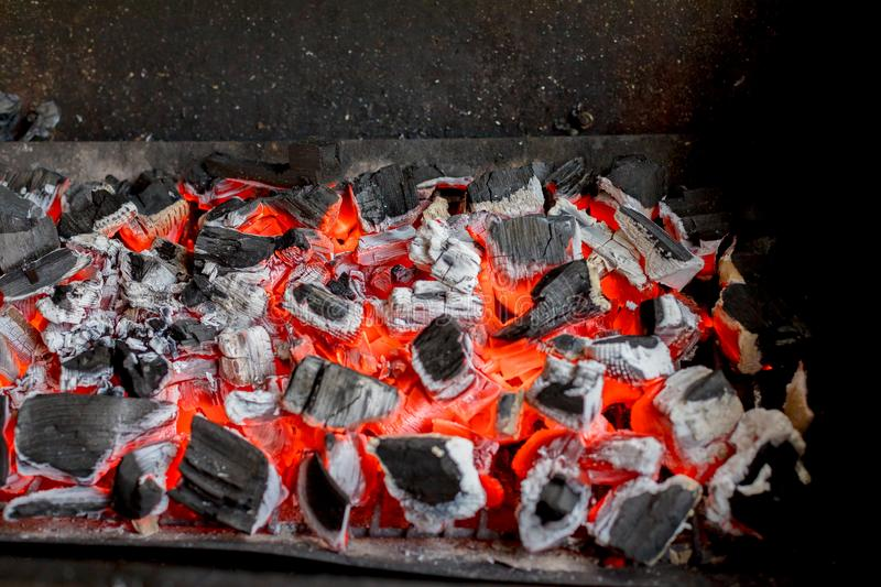 Bright hot coals and burning woods in bbq grill pit. Glowing and flaming charcoal, barbecue, red fire and ash. Weekend royalty free stock photography