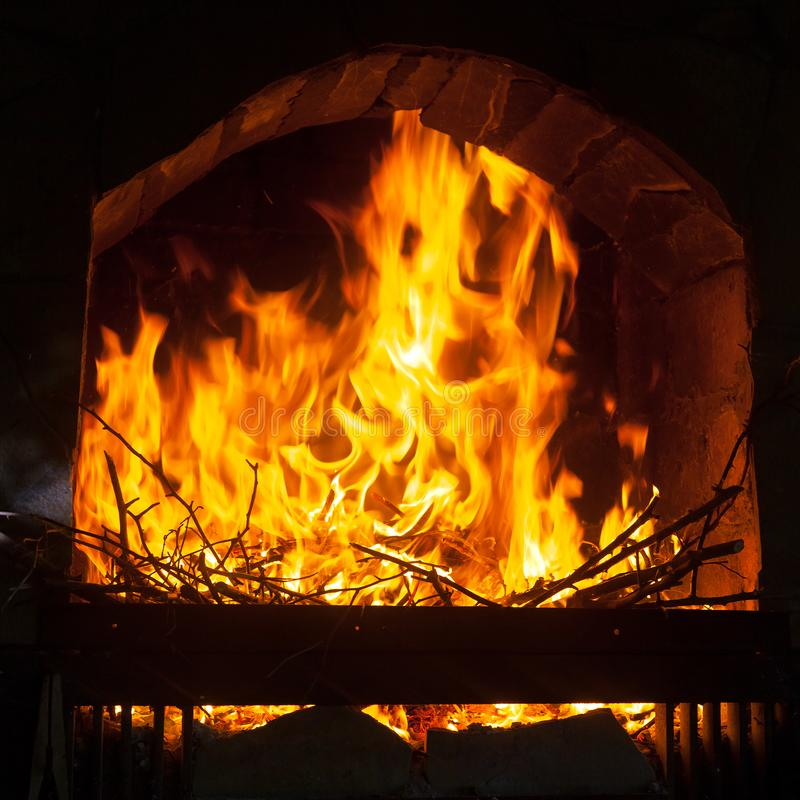 A bright and hot flame in the opening of a stone fireplace stock images