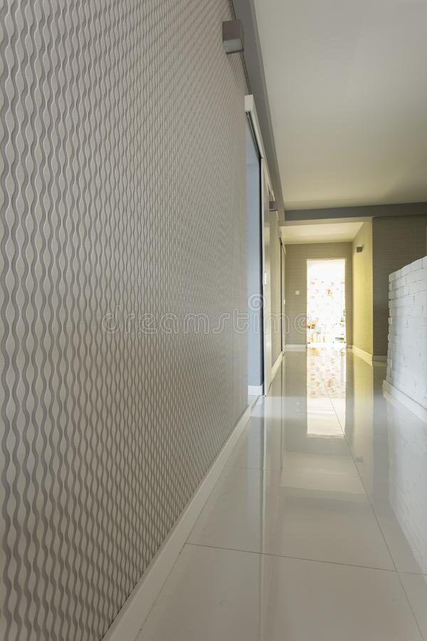 Bright house corridor with grey wallpaper. And white floor stock photos