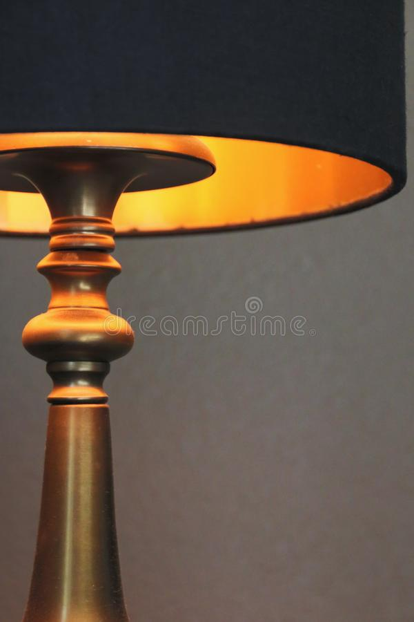 Close Up Partial View of an Illuminated Antique Brass Table Lamp Base with Black and Gold Lined Drum Shade. Bright Idea - Close Up Partial View of an Illuminated royalty free stock images