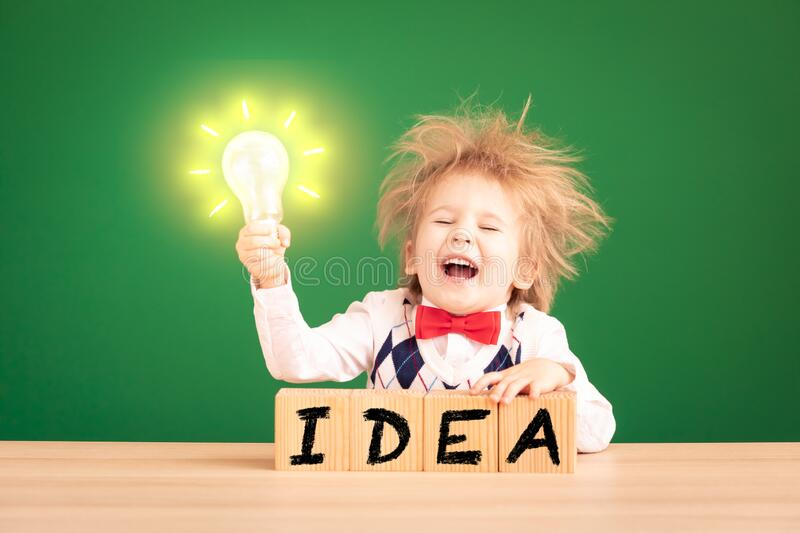 Bright idea! Happy child student against green chalkboard royalty free stock image
