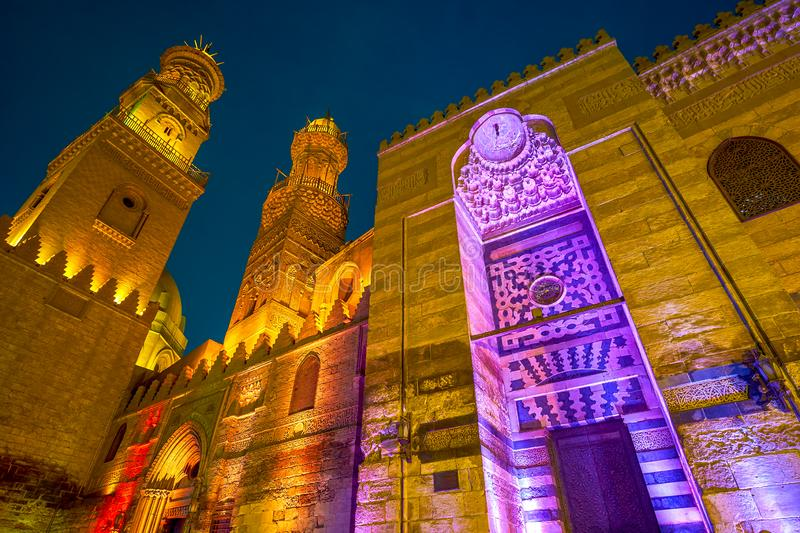 The evening in Cairo, Egypt. The bright illuminated minarets of medieval Qalawun complex in Al-Muizz stereet in Cairo, Egypt royalty free stock images