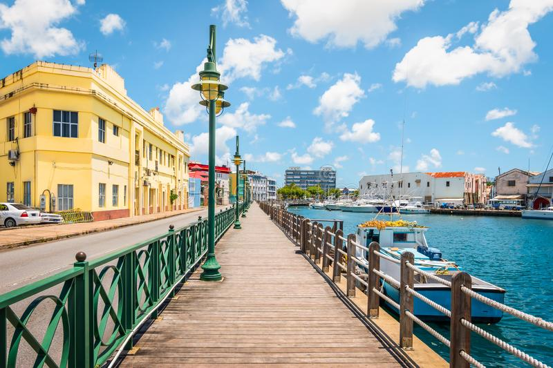 Promenade at marina of Bridgetown, Barbados. Bright image of wooden promenade with lanterns at the waterfront of Bridgetown in Barbados. Colorful building royalty free stock photo