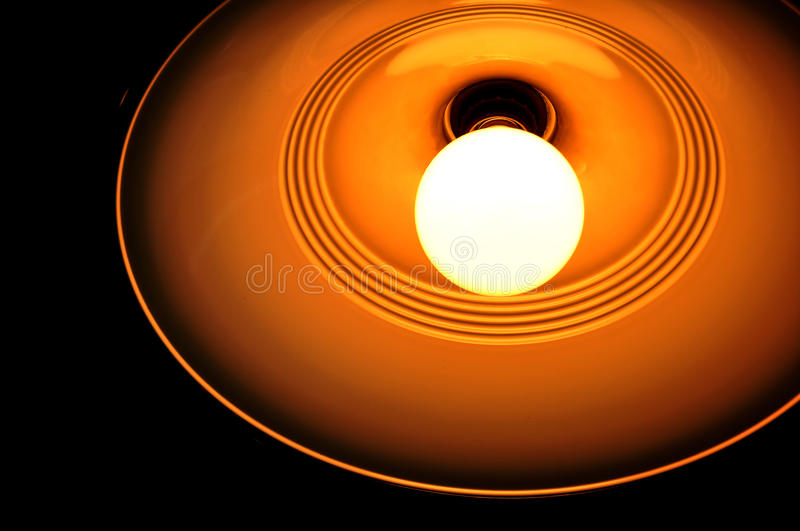 Bright Incandescent Light Bulb. A white hot incandescent light bulb glowing very brightly with an orange yellow light royalty free stock image