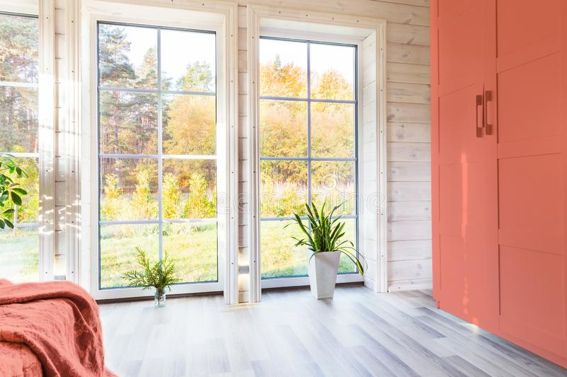 Bright interior, room in wooden house with large window. Scandinavian style. color of the year 2019 living coral pantone stock photo