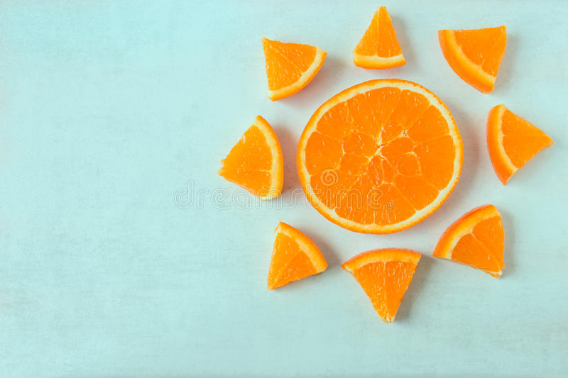 Bright juicy orange slices in the shape of a sun on a light back stock photos