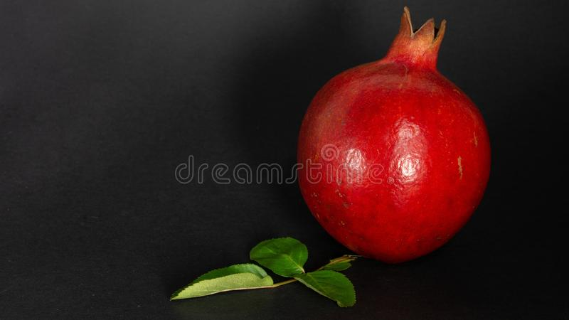Bright juicy pomegranate fruit, black background, in the photo the fruit is on the right side and on the left is an advertising sp royalty free stock photo